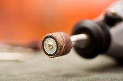Chiuda su del fuoco selettivo di un trapano grigio con gli accessori della perforazione sulla tavola grigia in un fondo vago Immagini Stock