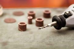 Chiuda su del fuoco selettivo di un trapano grigio con gli accessori della perforazione sulla tavola grigia in un fondo vago Fotografia Stock Libera da Diritti