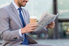 Chiuda su del giornale sorridente della lettura dell'uomo d'affari immagini stock