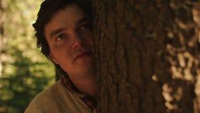 Chiuda su del giovane affascinato che guarda qualcuno nella foresta e nelle coperture il suo fronte dall'albero Storia di amore i archivi video