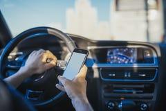 Chiuda su del giovane che esamina il navigatore di GPS dietro la ruota in automobile fotografia stock