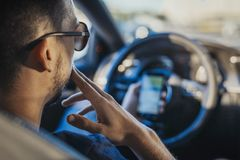 Chiuda su del giovane che esamina il navigatore di GPS dietro la ruota in automobile immagini stock