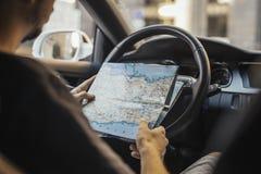 Chiuda su del giovane che esamina la mappa dietro la ruota in automobile fotografia stock libera da diritti