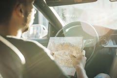 Chiuda su del giovane che esamina la mappa dietro la ruota in automobile immagini stock