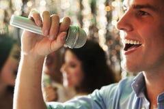 Chiuda su del giovane che tiene un microfono e che canta al karaoke, amici che cantano nei precedenti Immagini Stock