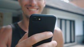 Chiuda su del giovane sorridente facendo uso di Smartphone, passando in rassegna in Internet o controllando le reti sociali al co stock footage