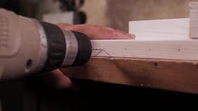 Chiuda su del lavoratore di legno che per mezzo di un trapano a mano elettrico per perforare un pozzo da parte a parte video d archivio