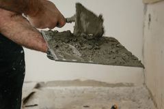 Chiuda su del lavoratore professionista del muratore dell'interno - porre le mattonelle fotografie stock