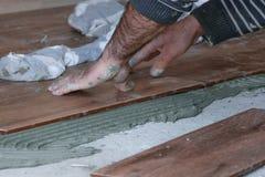 Chiuda su del lavoratore professionista del muratore dell'interno - porre le mattonelle sul pavimento al cantiere immagine stock libera da diritti