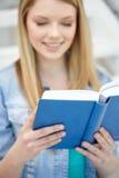 Chiuda su del libro di lettura della giovane donna alla scuola Immagine Stock