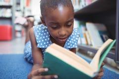 Chiuda su del libro di lettura della ragazza in biblioteca Fotografia Stock