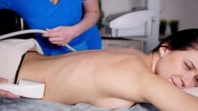 Chiuda su del massaggiatore professionista che massaggia il cliente s indietro con l'utensile speciale Massaggio di distensione stock footage