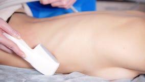 Chiuda su del massaggiatore professionista che massaggia il cliente s indietro e lo stomaco con l'utensile speciale Massaggio di  archivi video