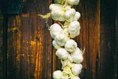 Chiuda su del mazzo di allium sativum bianco dell'aglio Tempo di raccolta asciugandosi sul fondo di legno Attaccatura da asciugar Immagini Stock Libere da Diritti