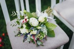 Chiuda su del mazzo nuziale di nozze con le rose sulla sedia Immagine Stock