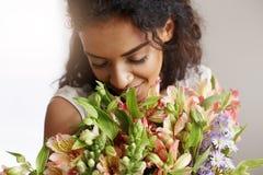 Chiuda su del mazzo sorridente di fiuto della tenuta del fiorista africano della ragazza dei alstroemerias Occhi chiusi Immagine Stock Libera da Diritti