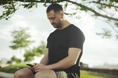 Chiuda su del messaggio di testo di battitura a macchina del giovane sul telefono cellulare all'aperto nel parco fotografia stock