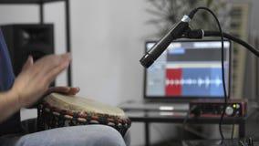 Chiuda su del musicista che gioca il djembe per tamburellare lo strumento nello studio domestico di musica video d archivio