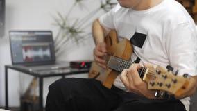 Chiuda su del musicista che gioca la chitarra elettrica nello studio domestico di musica stock footage
