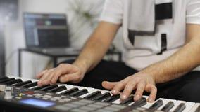 Chiuda su del musicista che gioca la tastiera del Midi nello studio domestico di musica stock footage