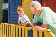 Chiuda su del nonno felice e del nipote che si appoggiano l'inferriata fotografia stock
