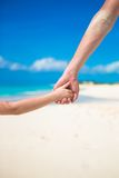 Chiuda su del padre e di piccola figlia che si tengono mani alla spiaggia Fotografie Stock