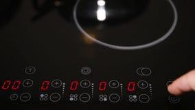 Chiuda su del pannello di controllo della cucina elettrica, dito maschio che gira sul temporizzatore archivi video