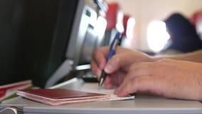Chiuda su del passeggero con il passaporto sta riempiendo nelle carte di arrivo o di migrazione nel volo piano di attimo 3840x216 archivi video