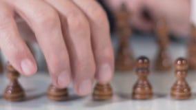 Chiuda su del pegno commovente della mano maschio nel gioco di scacchi, nell'affare e nella strategia politica stock footage