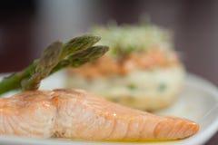 Chiuda su del piatto di color salmone con asparago Fotografia Stock