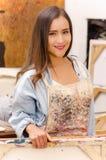 Chiuda su del pittore della donna che tiene una struttura vuota in sue mani, in un fondo della pittura dello studio Immagine Stock