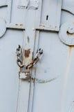 Chiuda su del portone bianco arrugginito con la serratura Immagine Stock