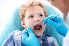 Chiuda su del ragazzo che fa i suoi esaminare denti da un dentista immagini stock