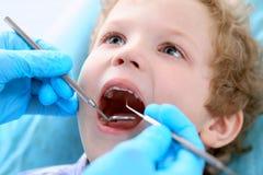 Chiuda su del ragazzo che fa i suoi esaminare denti da un dentista fotografia stock libera da diritti