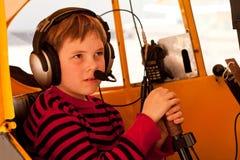 Chiuda in su del ragazzo che finge di pilotare il pifferaio Cub Fotografia Stock