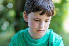 Chiuda su del ragazzo infelice che si siede all'aperto nel giardino fotografia stock