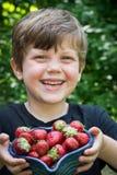 Chiuda su del ragazzo sveglio che sorride con gli stawberries fotografia stock