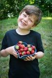 Chiuda su del ragazzo sveglio che sorride con gli stawberries immagine stock libera da diritti