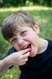 Chiuda su del ragazzo sveglio che sorride con gli stawberries fotografia stock libera da diritti