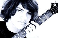Chiuda in su del ragazzo teenager con la chitarra bassa elettrica sopra bianco Fotografia Stock Libera da Diritti