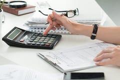 Chiuda su del ragioniere o del banchiere femminile che effettua i calcoli fotografia stock