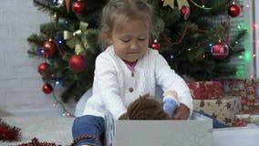 Chiuda su del regalo di Natale sveglio di apertura della bambina stock footage
