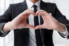 Chiuda su del ritratto dell'uomo d'affari che fa un cuore con le sue mani immagini stock
