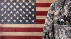 Chiuda su del rivestimento e dello stetoscopio dell'uniforme militare con rustico Fotografia Stock