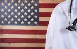Chiuda su del rivestimento e dello stetoscopio di medico con gli Stati Uniti rustici Immagini Stock Libere da Diritti