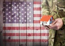 Chiuda su del soldato che tiene una piccola casa davanti alla bandiera americana immagine stock