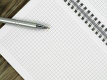 Chiuda su del taccuino in bianco e di una penna sulla scrivania di legno con lo spazio della copia immagini stock