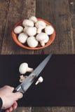 Chiuda su del taglio manuale dell'uomo dai funghi del coltello su un fondo di legno del bordo Fungo prataiolo bianco fresco in ci Fotografia Stock Libera da Diritti
