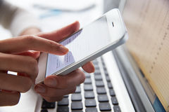 Chiuda su del telefono di Person At Laptop Using Mobile immagine stock libera da diritti