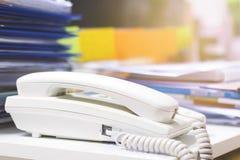 Chiuda su del telefono e dei lotti dei documenti non finiti sulla scrivania fotografie stock libere da diritti
